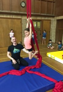 Student on silks with coach